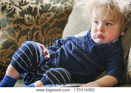 Toddler boy in dirty shirt laying and watching tv