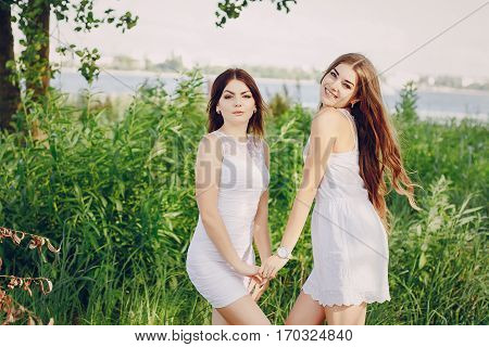 two girls resting on the beach. using communication. good time