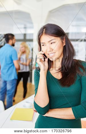 Woman as founder calling with cell phone in the office