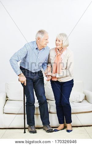 Old woman helping senior man getting up from a sofa at home