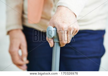 Wrinkled hand of old senior woman on a cane