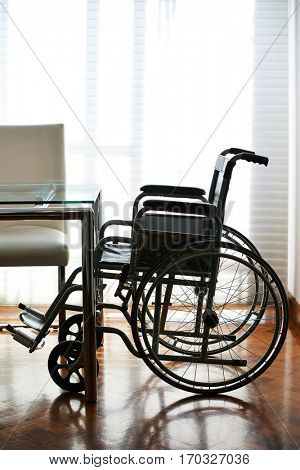 Empty wheelchair on a table in a nursing home