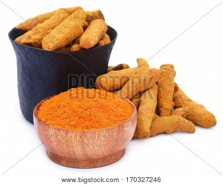 Whole and ground turmeric with mortar and pestle over white background