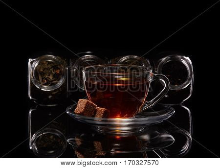 Various kinds of dry tea in glass jars and cup of aromatic tea standing on a black background.  Different kinds of tea leaves.