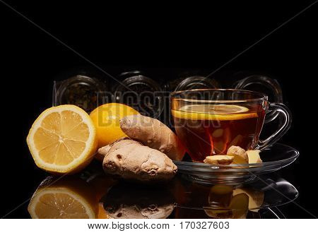 Various kinds of dry tea in glass jars and cup of aromatic tea with ginger and lemon standing on a black background.  Different kinds of tea leaves.