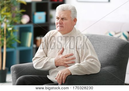 Aged man having heart pain, at home