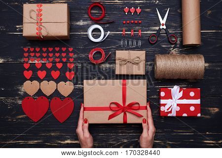 High angle of female hands holding ready-made gift box over settled decorative stuff. All needed materials to create valentine greeting box