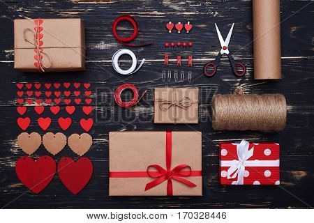 High angle of systematized decorative stuff using to create a present box for valentine day. Wrapping papers, ribbon, scissors, labels and other things isolated over grunge flat lay background
