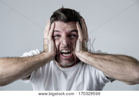 young attractive man sad and depressed suffering depression feeling sorrow and pain screaming desperate with hands on his face in sadness emotion concept