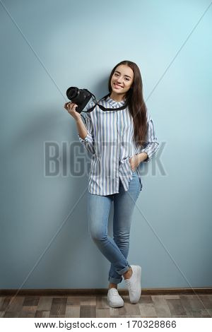 Beautiful young photographer near color wall