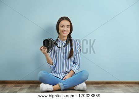 Beautiful young photographer sitting on floor near color wall