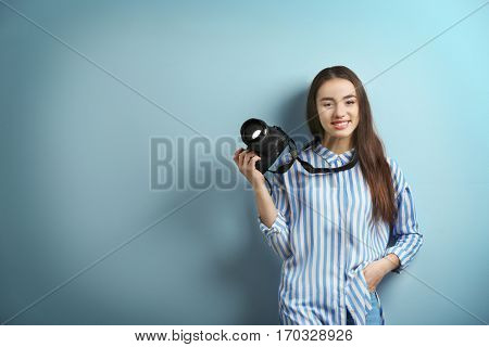 Beautiful young photographer on color background