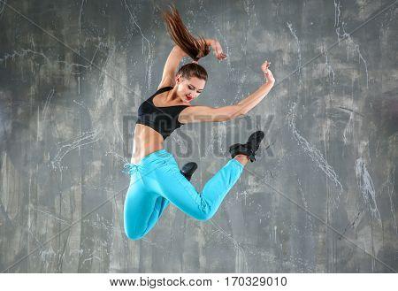 Hip hop dancer dancing on gray background
