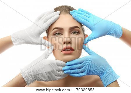 Hands touching female face on white background. Plastic surgery concept