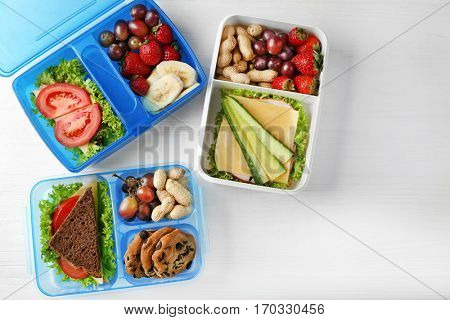 Lunchboxes with dinner on white wooden background