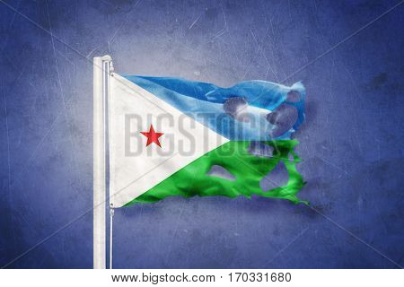Torn flag of Djibouti flying against grunge background.
