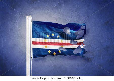 Torn flag of Cape Verde flying against grunge background.