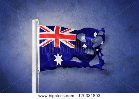 Torn flag of Australia flying against grunge background.