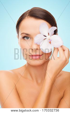 beauty, people, bodycare and health concept - beautiful young woman with orchid flower and bare shoulders over blue background
