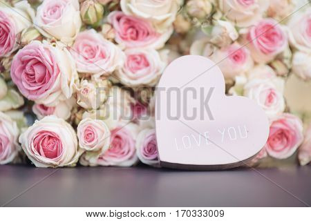 Love heart with I love you text, and bright pink roses background