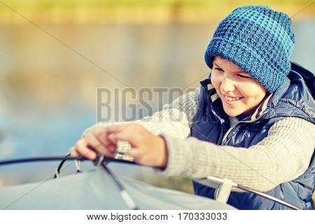 camping, tourism, hike and people concept - happy boy setting up tent outdoors