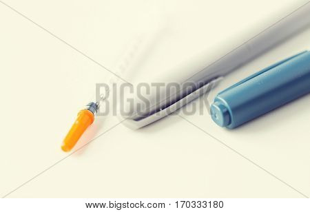 medicine, diabetes, medical tool and health care concept - close up of injection pen and disposable insulin syringe on table