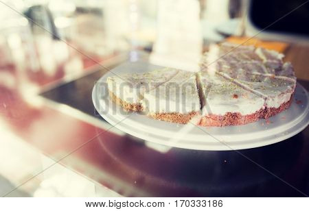 food, junk-food, culinary, baking and holidays concept - close up of cake on stand in cafe showcase or confectionery