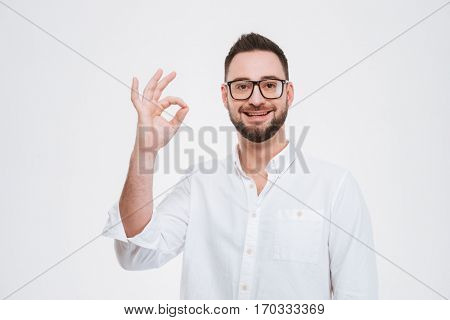 Image of smiling young bearded man dressed in white shirt wearing glasses posing with okay gesture isolated over white background.