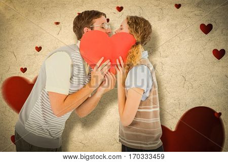 Geeky hipster couple kissing behind heart card against love heart pattern