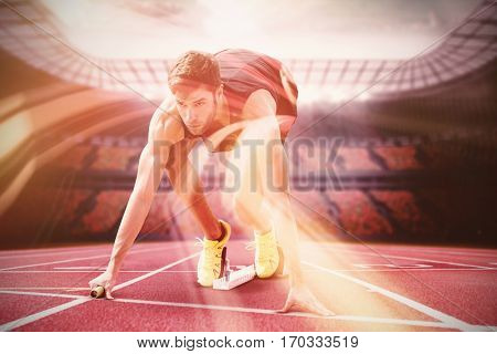 Focused sportsman at starting line on running track in stadium