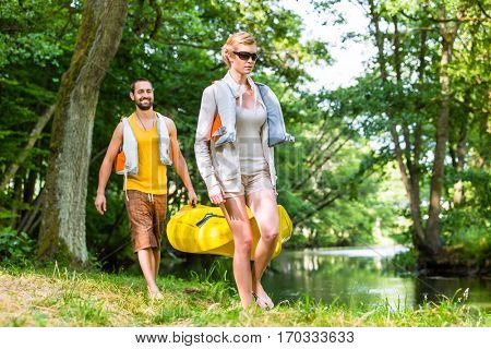 Woman and man carrying together kayak to forest river