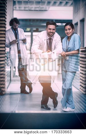 Portrait of doctor holding x-ray standing with nurse in hospital