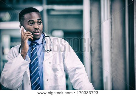Tensed doctor talking on mobile phone in hospital