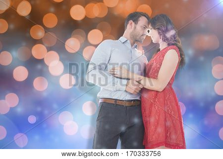 Young couple looking at each other and embracing against glowing background