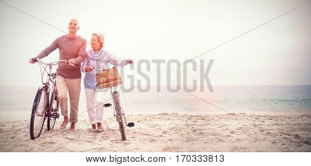 Full length of senior couple with their bicycles at the beach