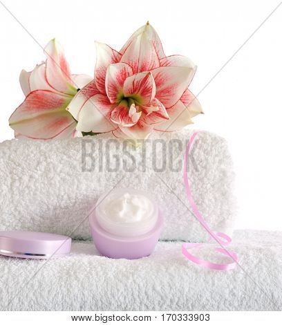 stacked white towels with pink flowers and cream isolated on white background