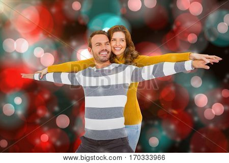 Young couple standing with arms outstretched against digitally generated twinkling light design