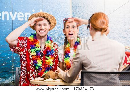 Tourists in travel agency anticipating vacation having good service rendered by operator