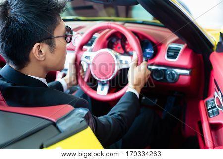 Asian man testing new sports car