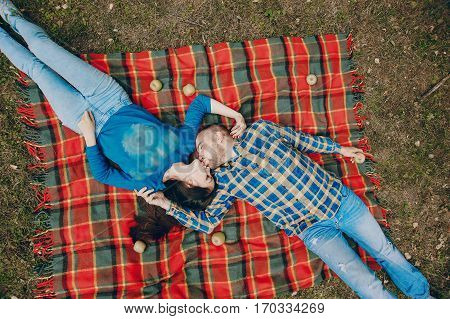 young couple relaxing in the park sitting on coverlet