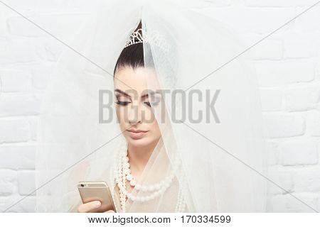 Young bride on wedding-day using mobilephone.