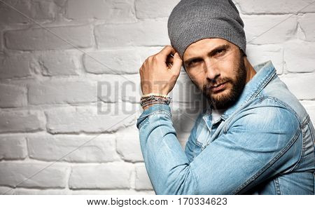 Trendy man in woolly hat standing against white brick wall. Looking at camera, copyspace.