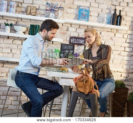 Young couple sitting in cafe, using tablet computer.
