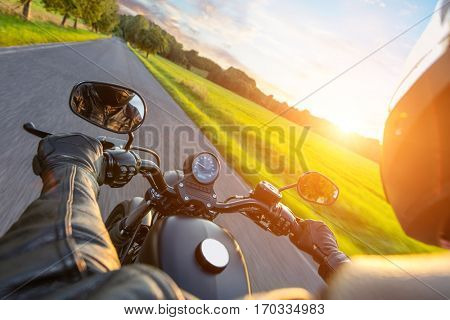 Chopper Driver riding motorcycle on an asphalt road in beautiful sunset light