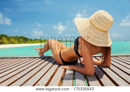 Young fashion woman relax on the beach. Happy island lifestyle. White sand, blue cloudy sky and crystal sea of tropical beach. Vacation at Paradise. Ocean beach relax, travel to Maldives islands