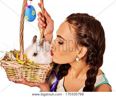 Easter girl holding bunny and eggs. Holiday style holding and group of rabbits in basket with flowers. Woman kiss rabbit. White background.