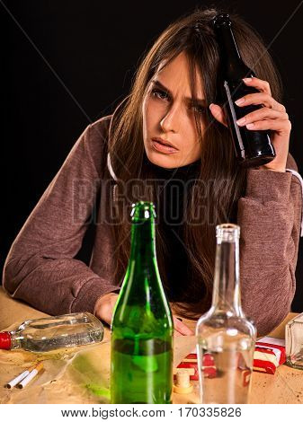Woman alcoholism is social problem. Female drinking is cause of poor health. She drinking alcohol in bad mood. Black background as a symbol of mourning. Table with empty bottle.