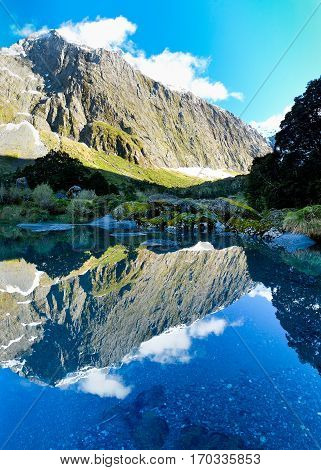 Mt Talbot Reflected in a Beautiful Blue Pond at Sunrise. Gertrude Valley, Fjordland National Park, Southern Alps, New Zealand.