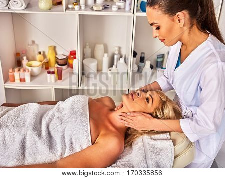 Facial massage for forty five year old woman. Portrait of woman middle-aged take face cleaning in spa salon. Interior with cosmetic background.