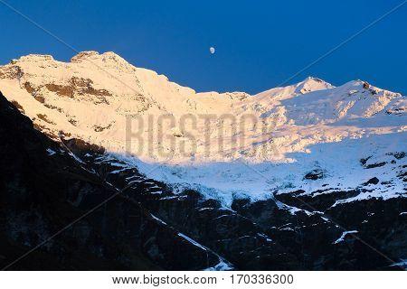 Sunrise Illuminates Mt Earnslaw's Glacier and The Moon. Aspiring National Park, Southern Alps, New Zealand.